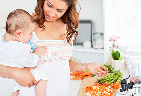 thinkstock_rf_mother_holding_baby_preparing_meal